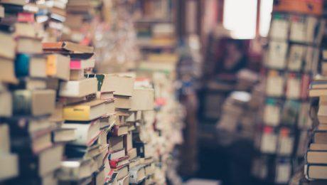 Książki ułożone w stosy na regałach
